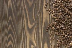 O fundo derramou feijões de café em uma tabela de madeira Fotos de Stock Royalty Free
