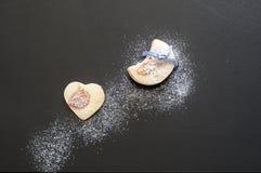 O fundo do alimento do inverno, cookies no fundo preto com açúcar de crosta de gelo gosta da neve Imagem de Stock