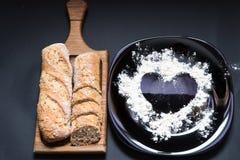 O fundo do cozimento com farinha e o coração dão forma na tabela do preto da cozinha de cima para do cozimento do dia de Valentim imagem de stock
