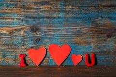 O fundo do dia de Valentim, ímã rotula i e u e três corações vermelhos no meio em um fundo de madeira Fotografia de Stock Royalty Free