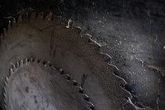 O fundo do metal escuro considerou as lâminas da serra circular velha com espiga imagens de stock