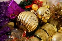 O fundo do Natal colorido e do ano novo é decorado com as bolas de brilho do ouro e o presente lilás do quadrado da cor, pássaro  foto de stock