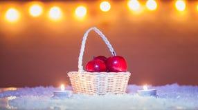 O fundo do Natal com a cesta com maçãs e velas vermelhas, neve, bokeh ilumina-se Foto de Stock