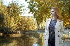 O fundo do outono, o lago, a menina olha na distância imagens de stock