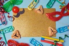 O fundo dourado do brilho de Purim com máscara do carnaval, traje do partido e hamantaschen cookies Imagem de Stock Royalty Free