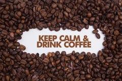 O fundo feito de feijões de café com ` da mensagem mantém a calma & bebe o ` do café Imagem de Stock