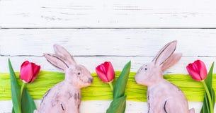 O fundo feliz da Páscoa com coelhos e mola das tulipas floresce na madeira branca com spcae da cópia Fotografia de Stock Royalty Free