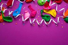 O fundo festivo do plano colorido material roxo da opinião superior dos confetes das flâmulas dos balões coloca o espaço da cópia foto de stock
