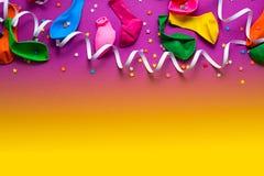 O fundo festivo do plano colorido material roxo da opinião superior dos confetes das flâmulas dos balões coloca o espaço da cópia imagens de stock royalty free