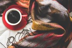O fundo home do inverno acolhedor, copo do café quente com marshmallow, aquece a camiseta feita malha no fundo branco da cama, to Imagem de Stock Royalty Free