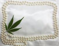 O fundo nupcial original do branco de cetim da hippie do casamento com pérolas molda e folha pressionada marijuana no canto Cartã Fotografia de Stock Royalty Free