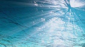 O fundo subaquático, raios de luz faz sua maneira através das ondas de oceano dos raios claros de alta qualidade dando laços da a video estoque