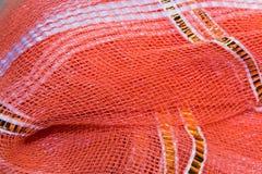 O fundo, textura da malha plástica vermelha com ouro Foto de Stock Royalty Free