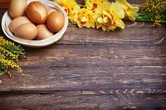 O fundo vazio da Páscoa com ovos da páscoa e mola floresce fotos de stock