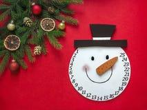 O fundo vermelho uma disposição em um canto do abeto ramifica e ornamento do Natal e encontra-se no centro a cabeça de um advento fotografia de stock