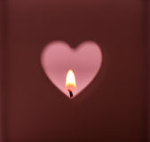 O furo das formas do coração cortou na obscuridade - luz ardente da vela do fundo vermelho no contexto cor-de-rosa, romântico, me Fotografia de Stock