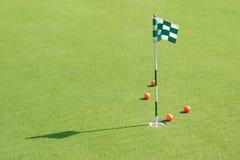 O furo do golfe com bandeira e bolas de golfe na grama verde do golfe co Foto de Stock