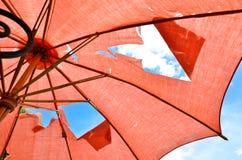 O furo no guarda-chuva vermelho Imagens de Stock Royalty Free