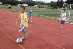 O futebol de jogo dos meninos no centro de esportes do shekou de shenzhen Fotografia de Stock