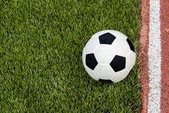 O futebol está perto da linha no campo de futebol artificial da grama Fotografia de Stock Royalty Free
