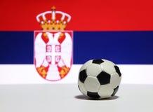 O futebol pequeno no assoalho branco com cor azul e vermelha branca, focaliza para fora a imagem da águia e da coroa da bandeira  Foto de Stock Royalty Free