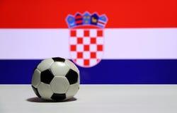 O futebol pequeno no assoalho branco com para fora focaliza a cor branca e azul vermelha do fundo croata da bandeira da nação Foto de Stock