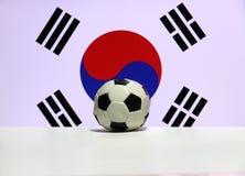O futebol pequeno no assoalho branco com Yin Yang vermelha e azul e quatro trigrams pretos da nação coreana sul embandeiram o fun imagem de stock