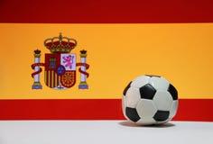 O futebol pequeno no assoalho branco e a nação espanhola embandeiram o fundo fotografia de stock