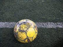 O futebol velho no relvado artificial Fotos de Stock