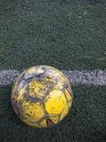 O futebol velho no relvado artificial Fotografia de Stock Royalty Free