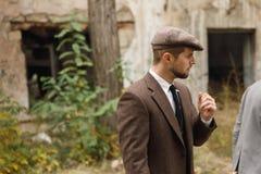 O gângster olha alguém, estando pela construção abandonada retro outdoors imagem de stock royalty free