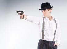 O gângster perigoso no chapéu aponta uma pistola Fotografia de Stock Royalty Free