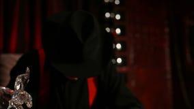 O gângster que senta-se em uma tabela que fuma um charuto e esconde sua cara sob um chapéu video estoque