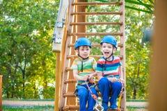 O gêmeo incomoda-se escalar no parque da aventura é um lugar que possa conter uma grande variedade de elementos, tais como exercí imagens de stock