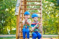 O gêmeo incomoda-se escalar no parque da aventura é um lugar que possa conter uma grande variedade de elementos, tais como exercí imagem de stock royalty free
