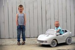 O gajo pequeno do ute do  de dois Ñ joga com um carro do brinquedo fotografia de stock royalty free