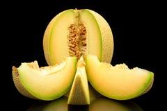 O galia do melão entalhado com fatias isolou o preto no estúdio fotos de stock royalty free