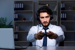 O gamer do homem de negócios que fica tarde para jogar jogos imagens de stock royalty free
