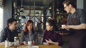 O garçom amigável no avental está servindo copos das bebidas aos jovens que socializam no café que senta-se na tabela Alimento e  video estoque