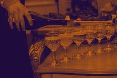 O garçom derrama o champanhe na tabela de bufete efeito do duotone foto de stock