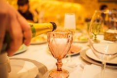 O garçom derrama o champanhe no vidro imagens de stock