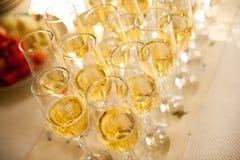 O garçom derrama o champanhe nos vidros na tabela imagens de stock