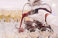 O garçom derrama o suco de fruta da bebida nos vidros Foto de Stock Royalty Free