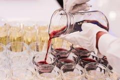 O garçom derrama o suco de fruta da bebida nos vidros Foto de Stock