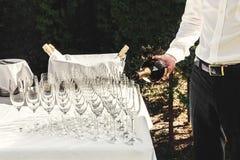 O garçom derrama vidros luxuosos à moda para o champanhe em uma tabela para fotografia de stock
