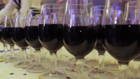 O garçom derrama o vinho em vidros em um partido video estoque