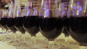 O garçom derrama o vinho em vidros em um partido filme