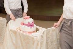 O garçom dois leva o bolo de casamento com rosa do vermelho fotos de stock