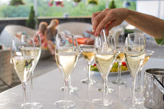 O garçom joga uma cobertura em vidros de vinho Fotografia de Stock
