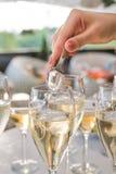 O garçom joga uma cobertura em vidros de vinho Fotos de Stock